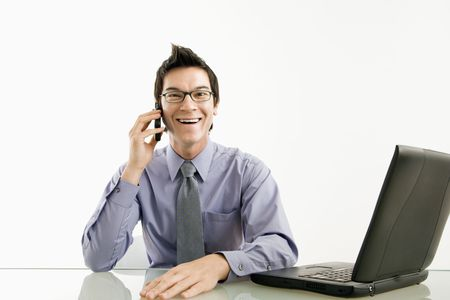 Smiling Asian businessman sitting at desk talking on cellphone. photo