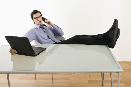 Asian businessman sitting at desk talking on cellphone and using laptop. photo