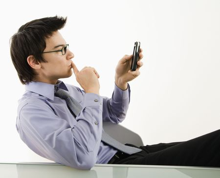 Asian businessman sitting at desk texting using his pda cellphone. Stock Photo - 3569378