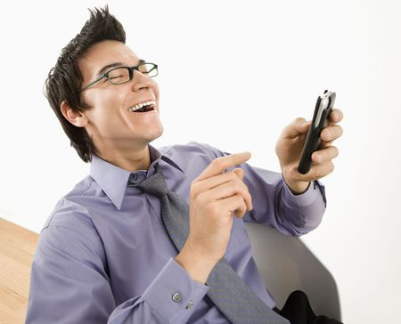 Laughing Asian businessman sitting at desk texting using his cellphone. Stock Photo