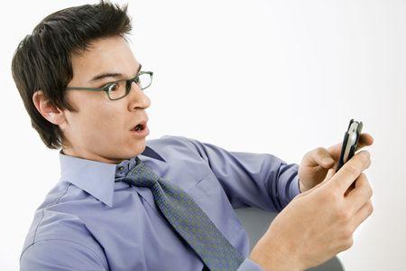 cara sorpresa: Asia empresario con expresi�n sorprendido buscando en su mensaje sobre pda m�vil.