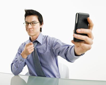 vanity: Businessman taking photograph of himself using pda or mobile phone deivice.