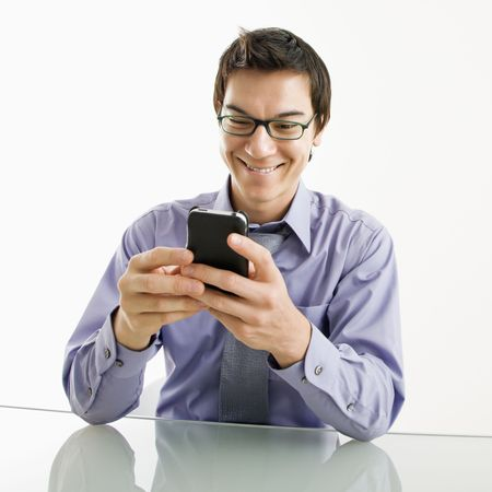 Smiling Asian businessman sitting at desk texting using his pda cellphone. Stock Photo - 3569374