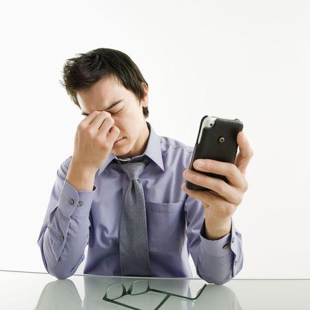 疲れて彼をこすりアジア系のビジネスマンの目彼の pda 携帯電話。 写真素材 - 3569393