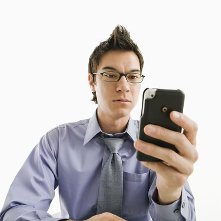 Asian businessman with seus expression looking at his pda cellphone. Stock Photo - 3569475