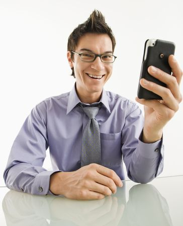 Smiling Asian businessman with his pda cellphone. photo