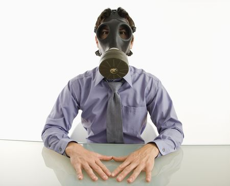 Businessman sitting in white room wearing gas mask. Stock Photo - 3569360