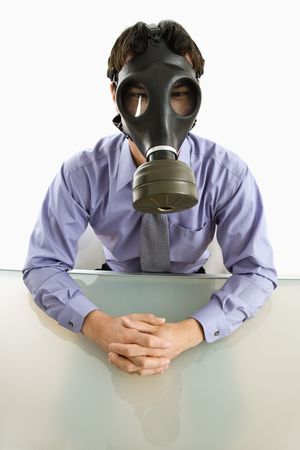 Businessman sitting in white room wearing gas mask. photo