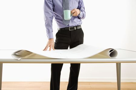Business man standing with coffee cup next to table with blueprints. photo