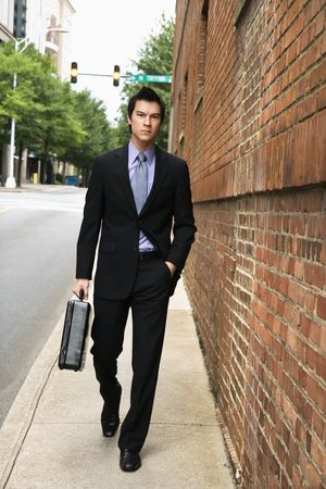 Asian business man walking down sidewalk in the city.