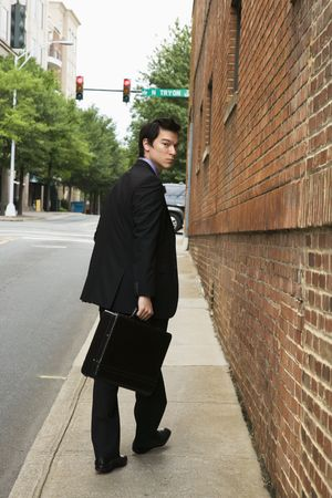 Asian business man walking down sidewalk in the city looking back at viewer. photo