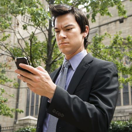 phone business: Asian business man standing looking at cell phone messages.