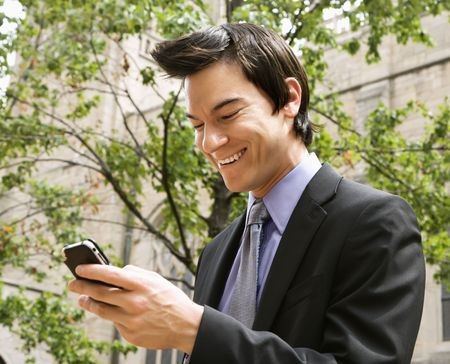 Asian business man standing looking at cell phone messages laughing.