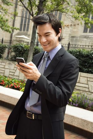 Asian business man standing looking at cell phone messages smiling. photo