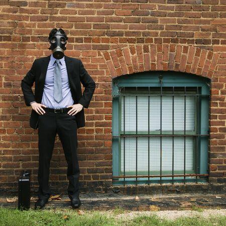 gas mask: Empresario de pie junto a la pared de ladrillos usando m�scara de gas.