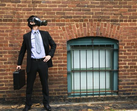 Businessman standing next to brick wall  and looking off to side wearing gas mask. Stock Photo