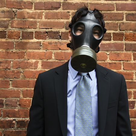 Businessman standing next to brick wall wearing gas mask. photo