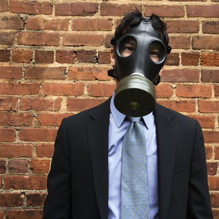 Businessman standing next to brick wall wearing gas mask. Stock Photo - 3569637