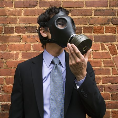 Businessman standing next to brick wall  and looking off to side wearing gas mask. photo