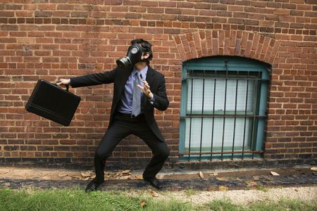 Businessman standing next to brick wall wearing gas mask in fighting stance. photo