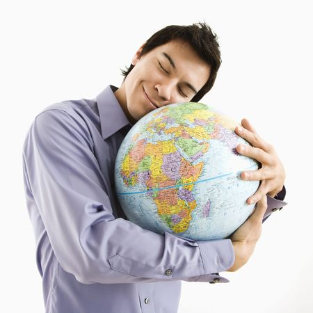 Young Asian man holding globe with happy expression on his face.