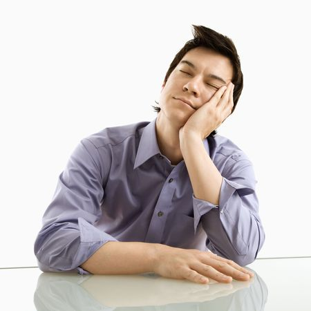 Young Asian business man sitting resting his eyes. Stock Photo