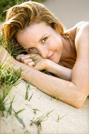 Close up portrait of attractive redheaded woman lying in grassy sand looking at viewer. photo