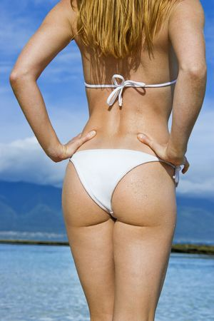 Rear view of pretty redheaded female standing on beach wearing bikini looking out at the ocean.