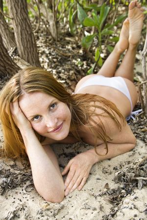 Redheaded woman sitting on ground wearing bikini looking at viewer. photo