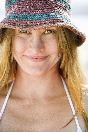Close up portrait of smiling attractive young redheaded woman wearing hat and bikini top. photo