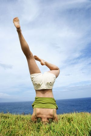 Young woman doing headstand in grass near ocean in Maui, Hawaii. photo