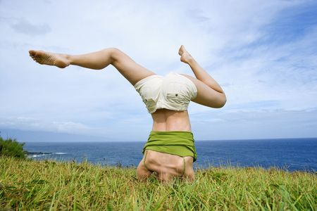 headstand: Young woman doing headstand in grass near ocean in Maui, Hawaii.
