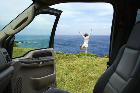 excited woman: Excited woman standing on grassy cliff by Pacific Ocean in Maui, Hawaii. Stock Photo