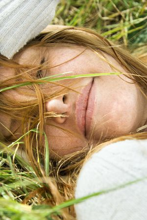 Close up portrait of attractive young redheaded woman lying in grass resting. photo