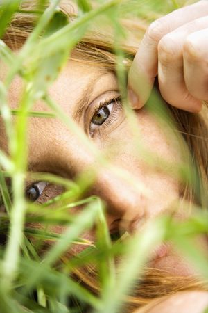Close up portrait of pretty redhead lying in grass looking at viewer. Stock Photo - 3569568