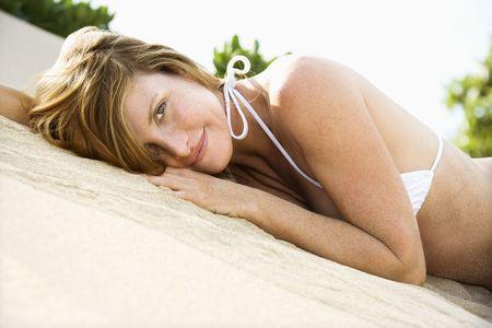 Portrait of pretty redheaded female lying in sand wearing bikini. photo