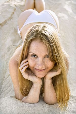 Portrait of pretty redheaded female lying in sand wearing bikini. photo