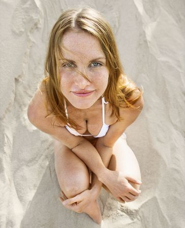 High angle view of redheaded woman sitting on beach wearing bikini looking at viewer. photo