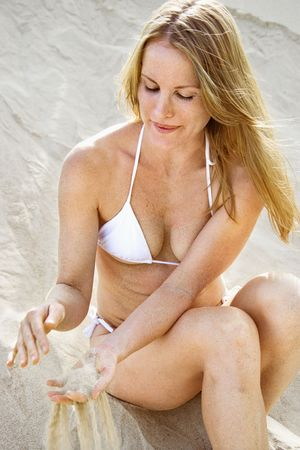 Pretty redheaded female sitting on beach wearing bikini and sifting sand through her fingers. photo