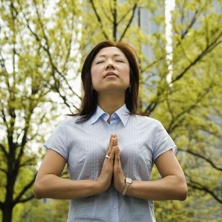 Mid-adult Asian woman standing outside with trees and skyscrapers behind her meditating. photo