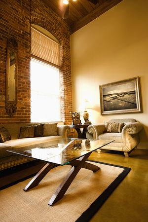 Interior of living room with large window, brick wall, coffee table, and sofa. Stock Photo - 3569665