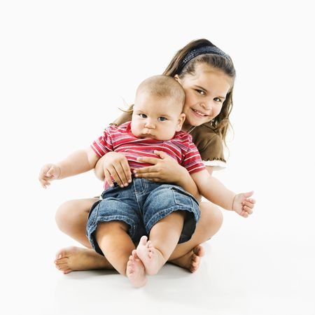 Cute little hispanic girl holding baby brother in her lap. Stock Photo - 3569390