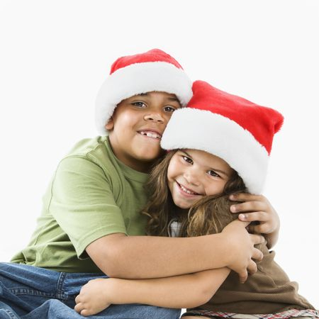 little girl smiling: Hispanic brother and sister wearing santa hats hugging