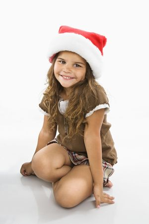 Little hispanic girl sitting on floor wearing santa hat. photo
