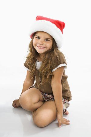 Little hispanic girl sitting on floor wearing santa hat.