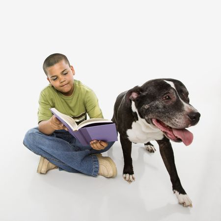 only one boy: Young hispanic boy reading book while his dog sits nearby. Stock Photo