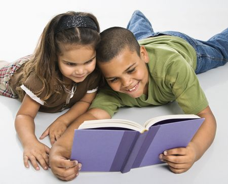 Hispanic brother and sister reading book together sitting on floor. Stock Photo - 3569579