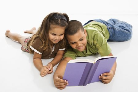 sitting on floor: Hispanic brother and sister reading book together. Stock Photo