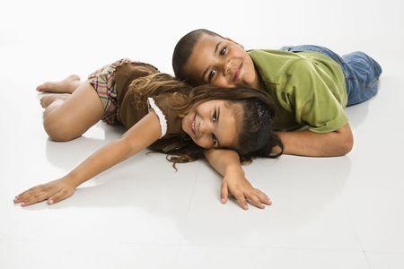 hispanic boy: Retrato de Hispanic hermano y hermana se extiende en el piso sonriendo en el espectador.