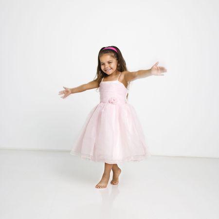 Cute little hispanic girl wearing pink dress dancing. photo